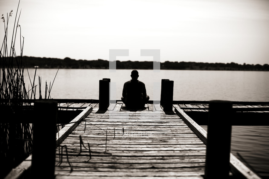 A man sitting on a dock looking out at the water