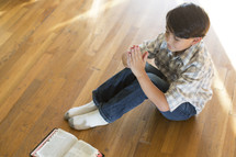 boy sitting on the floor with hands held in prayer