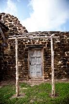 arbor in front of an old wood door