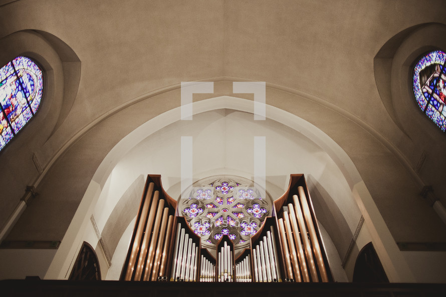 The ceiling of a chapel - organ pipes fill the bottom of the photo