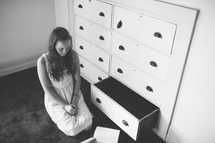 woman kneeling in prayer in front of open dresser