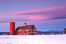 Red barn in the snow with the Colorado front range in the background