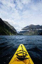Front of a kayak on the open waters heading toward the mountains