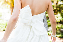Back of women's dress bridal gown with large white bow