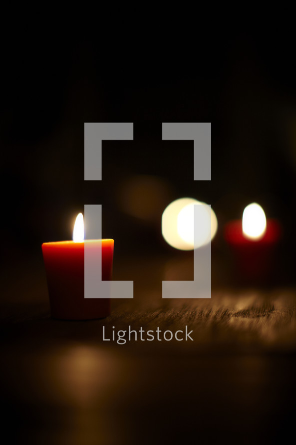 Lit votive candles on wood planks.