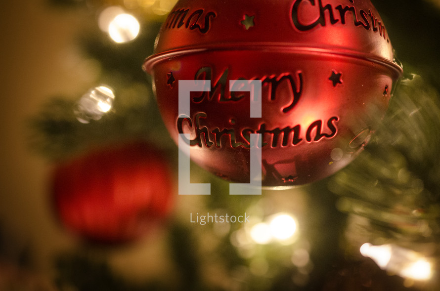 Red metal Christmas ornament with Merry Christmas hanging on Christmas tree.