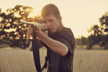 A young man aiming a rifle.