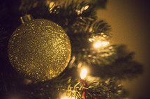 gold glitter ball Christmas ornament on a Christmas tree