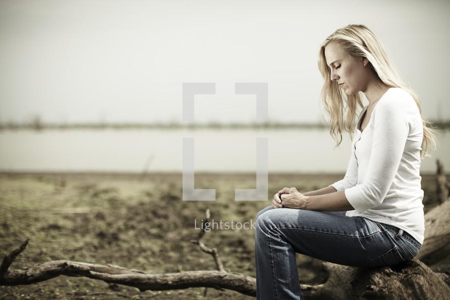 A woman practicing solitude & silence near a lake