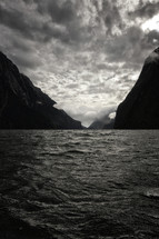 A New Zealand bay surrounded by mountains and storm water with dark clouds