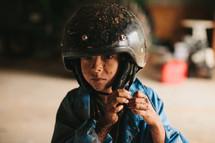 A muddy boy wearing a helmet