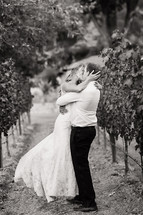 Bride and groom kissing outdoors in a vineyard embrace, love romance wedding napa valley