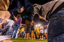 Young men holding hands in prayer salvation crusade kneeling on bender knee