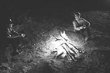 friends sitting beside a bonfire