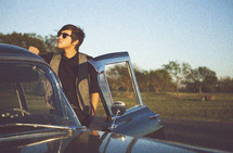 man in sun glasses with his hand on the roof of an old car