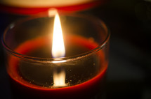 Lit, red votive candle.