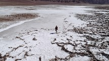 person hiking a dry lake bed
