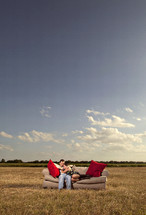 Couple on couch in outdoor grass field