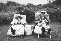 elderly couple reading together in lawn chairs