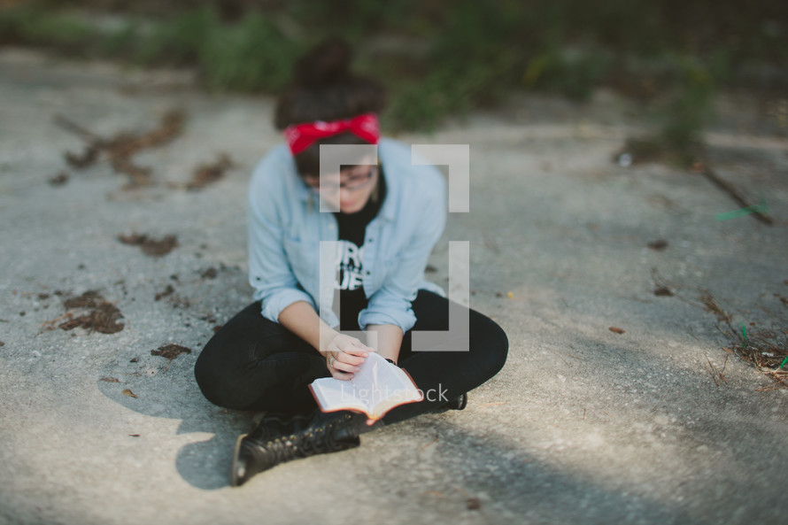 woman sitting on a rock reading a small Bible