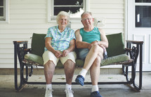 elderly couple sitting on a porch swing
