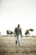 A man smiling and walking through a field