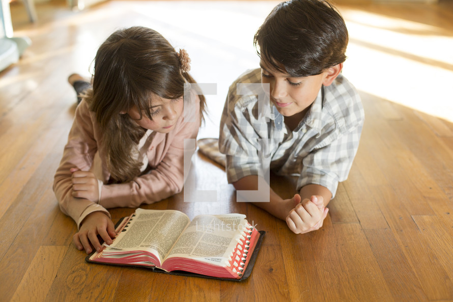 Siblings reading the Bible together