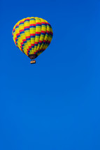 A brightly colored hot air balloon in a blue sky one