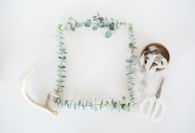 eucalyptus frame, antlers, scissors, and spool of ribbon in a bowl