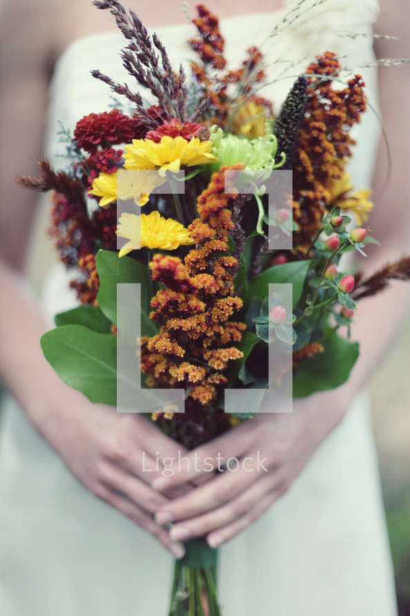 Woman's hands holding bouquet of wildflowers.