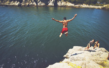 Male jumping off rock cliff into lake