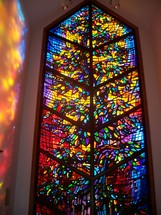 A stained glass window reflects light on the walls of the church providing a warm glow of light and a prism of colors showing the light and love of Heaven.