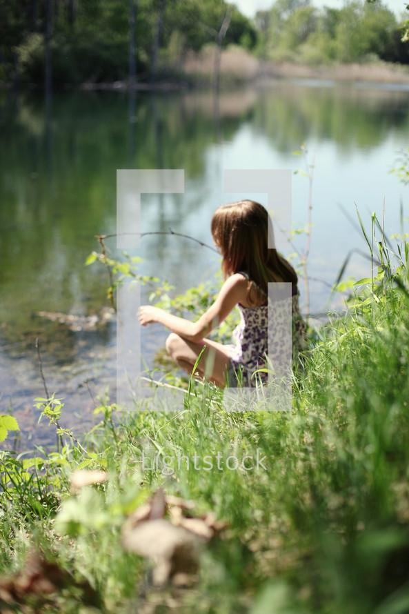 Girl sitting beside pond