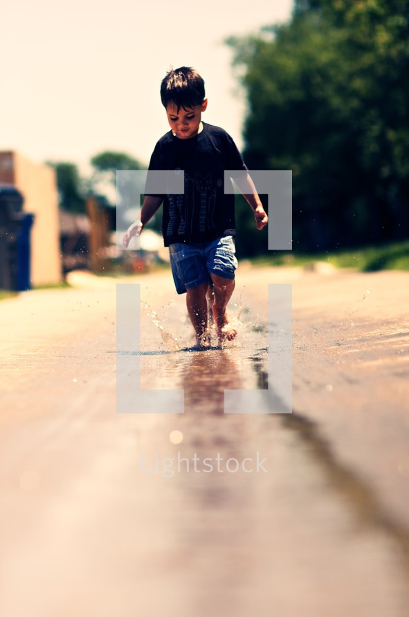 Young boy playing in water with bare feet