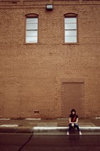 Girl sitting on a sidewalk in front of a brick building
