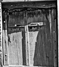 Wooden cross nailed to wooden door