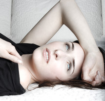 Angel Eyes; woman with blue eyes lying on bed with arm on forehead, pillows in background.