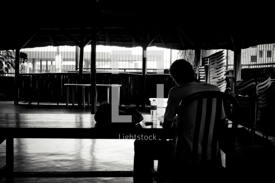 A shot from behind of a man sitting at a desk