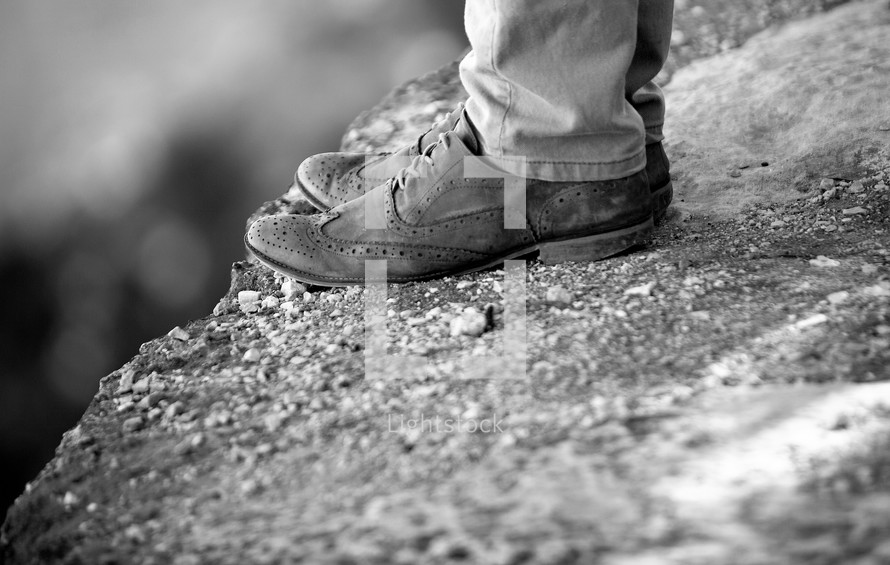 A man standing on the edge of a cliff with brown wingtip shoes