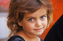Kurdish Girl with big eyes smiling against orange background. 