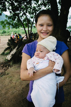 a young girl holding an infant