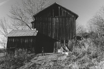 A child stands in front of an old wood barn in the countryside of Pennsylvania
