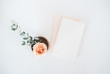 rose in a wooden bowl and stationary