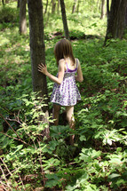 child walking through overgrowth in on a forest floor