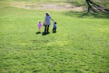 A mother holding hands and walking with her children in a field of grass.