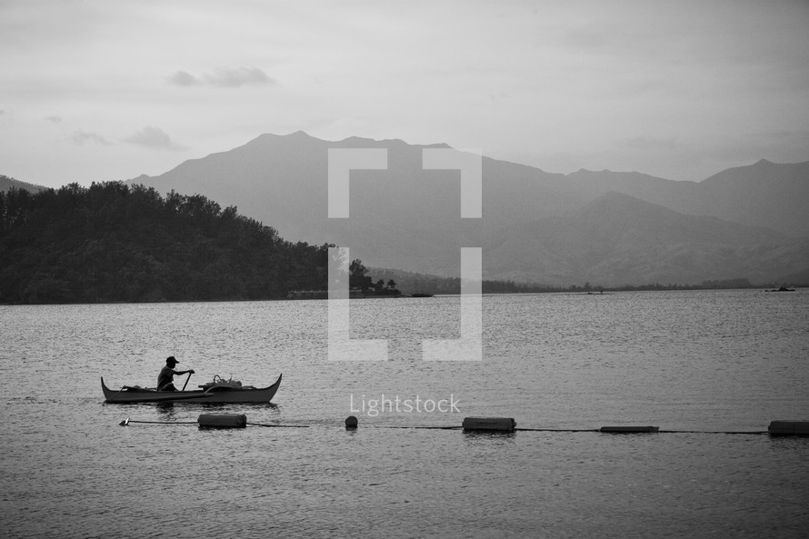 Man canoeing on open lake with mountain backdrop