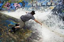 man skateboarding on a ramp at graffiti covered skateboard park