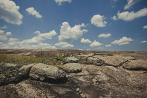 white puffy clouds over rocky ground
