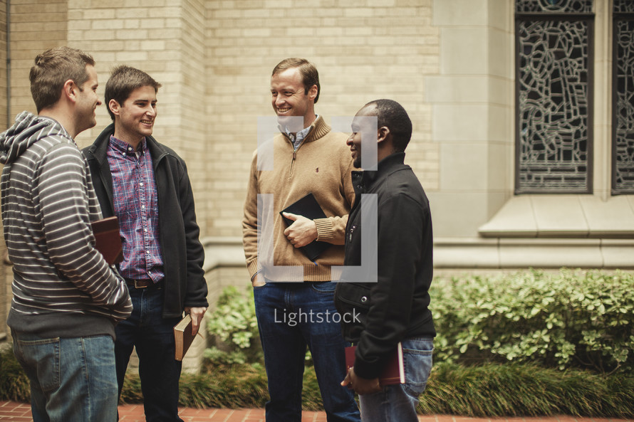 four men standing in front of a church holding Bibles