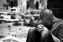 A young man prays on a rooftop.